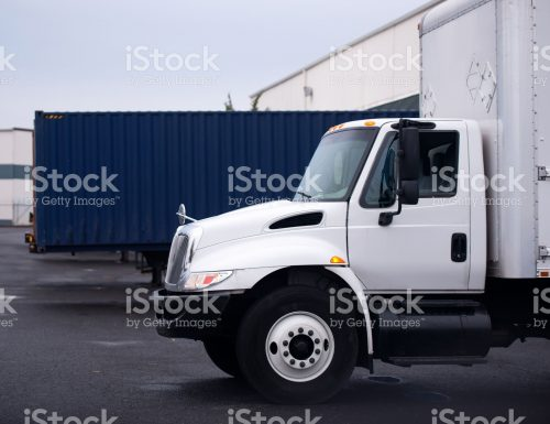 Small economical truck with a box for the local delivery of goods on the parking lot near the store in anticipation of loading or unloading of commercial cargo.
